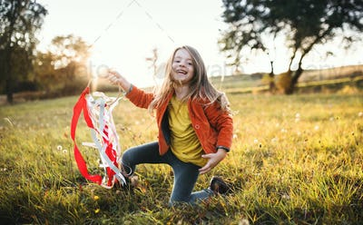 A small girl playing with a rainbow hand kite in autumn nature at sunset.