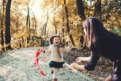 A young mother with a toddler daughter running in forest in autumn nature.