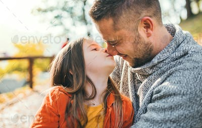 A young father having fun with a small daughter in autumn nature.