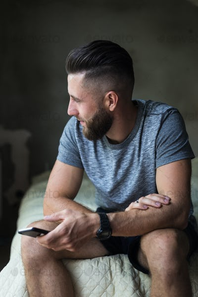 Confident bearded man is sitting on couch and typing on smartphone