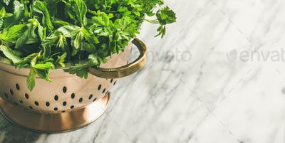 Bunch of fresh garden herbs in brass colander, copy space