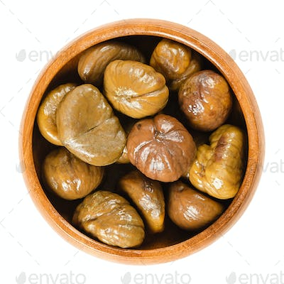 Cooked sweet chestnuts in wooden bowl over white