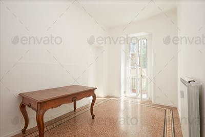 White room with wooden table in renovated apartment