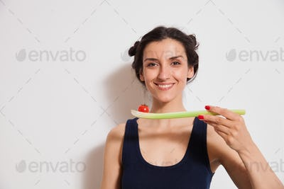Young woman holding delicious tomato on celery stick