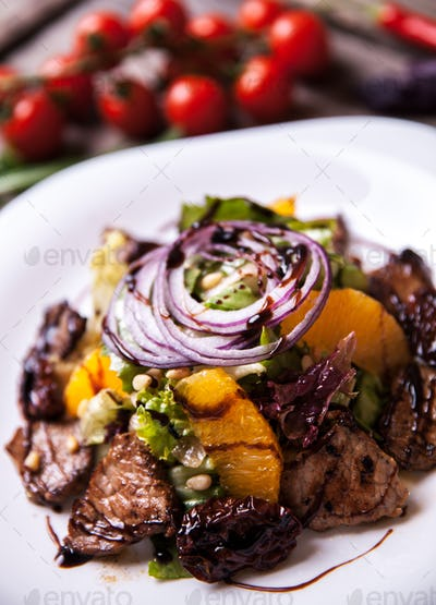 Salad with veal and orange slices and fresh herbs