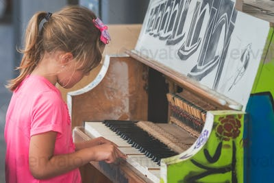 Cute little girl playing on the piano