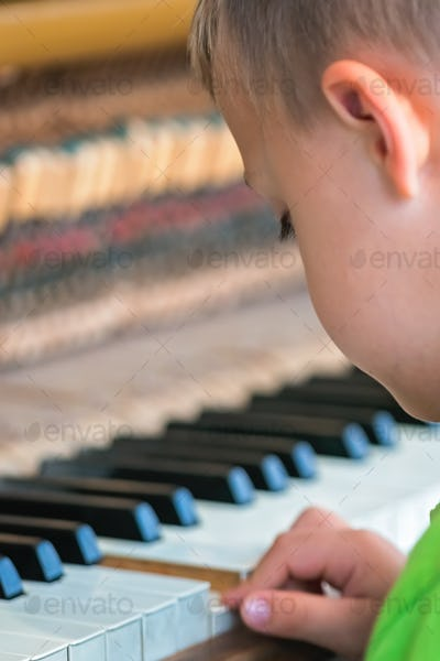 Little boy playing on the piano
