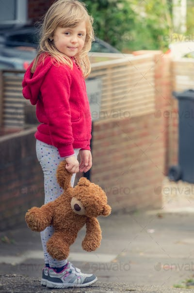 Adorable girl holding teddy bear