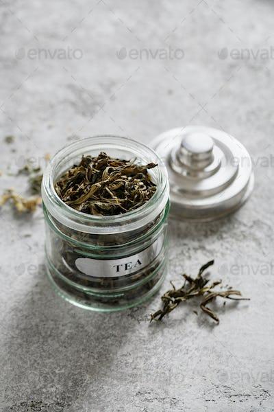 Green tea in jar on a grey background