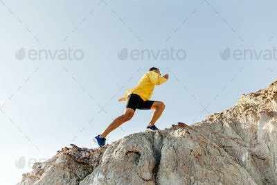 man in sports clothes climbing steep mountain