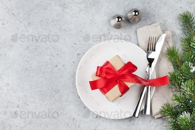 Christmas table setting with gift box and fir tree