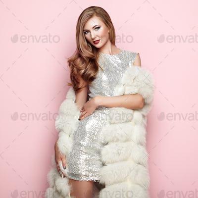 Fashion portrait young woman in white fur coat