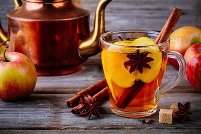 Hot mulled apple cider drink with cinnamon stick, cloves and anise