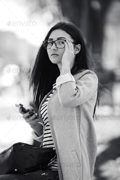 model in the middle of the city with phone