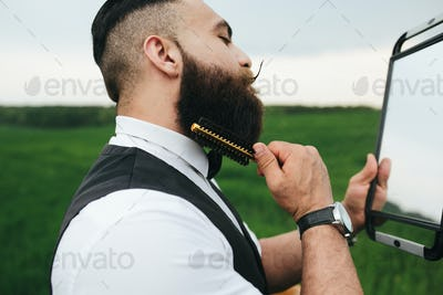 A bearded man preparing to shave in the field