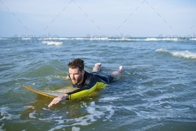 Surfer paddling through the water