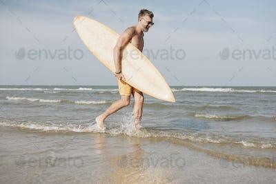 Mature man carrying a surfboard