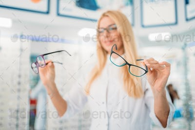 Female optician against showcase with glasses