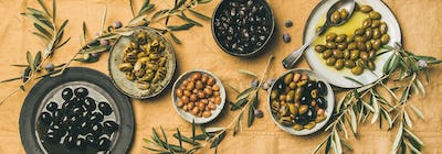 Flat-lay of mediterranean meze olives appetizers on yellow table cloth