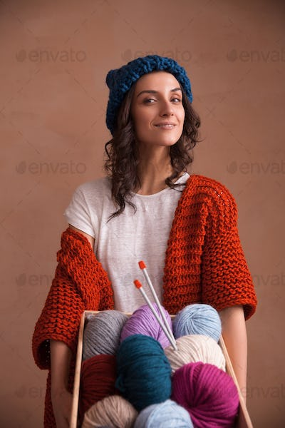 Woman holding the box witn yarn clews and knitting needles