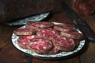 Spanish sausage on porcelain dish on rustic wood