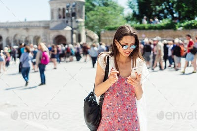 beautiful young girl in a dress and sunglasses reading a message