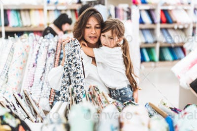 Mom and daughter in the fabric store choose fabric