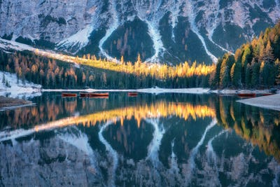 Braies lake with reflection in water at sunrise in autumn