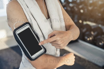 Young sport woman in gym using smartphone