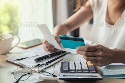 Young woman checking bills, taxes, bank account balance and calculating credit card expenses at home