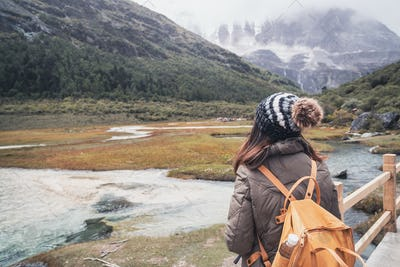 Hiking young woman traveler with backpack looking beautiful landscape, Travel lifestyle concept