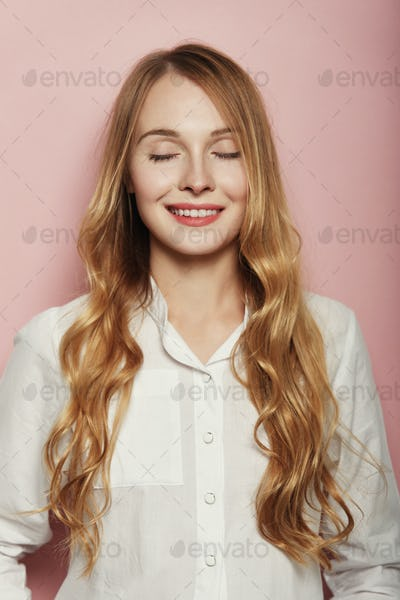 Pretty young woman posing on pink background