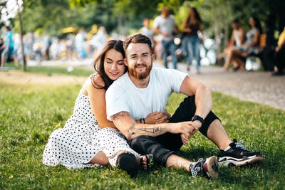 Beautiful young girl hugging her handsome guy in the park.