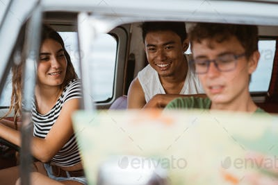 young people inside car using a map