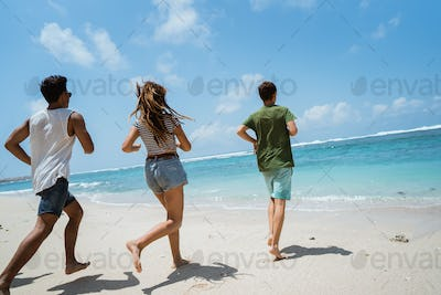 young man and woman run to the beach
