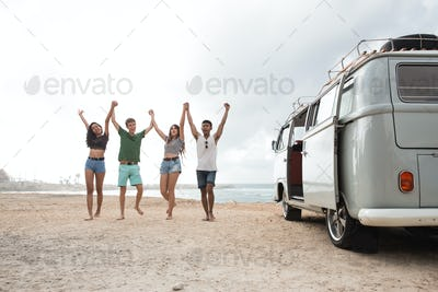 Happy friends walking at beach and rise up hands