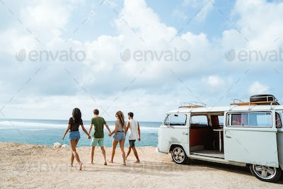 Friends holding hands and walking in beach on a sunny day