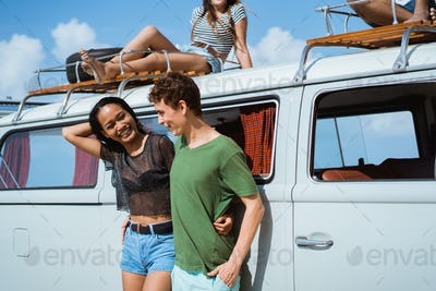 Hipster girl relaxing with friends in her summer road trip, care