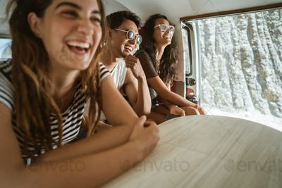 Carefree hipster having fun inside retro van on trip