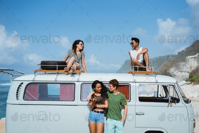 Hipster girl relaxing with friends on the retro van roof