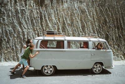 young people push broke down retro van
