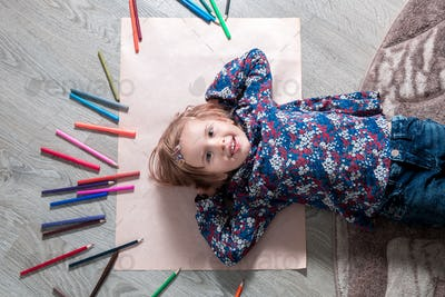 Child lying on the floor on paper looking at the camera