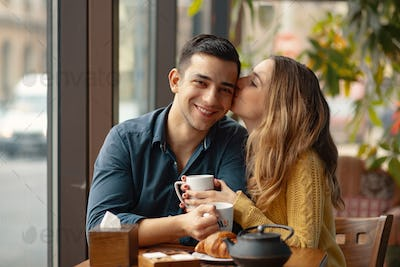 Young couple in love sitting in a cafe, drinking coffee