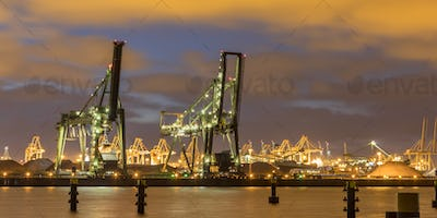 Industrial harbor landscape with  two loading cranes at night