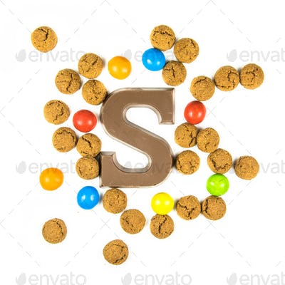 Chocolate letter S with bunch of scattered pepernoten cookies