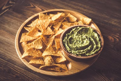 Guacamole with tortilla chips on the wooden tray