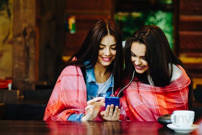 Two girl sitting listening to music with a smartphone