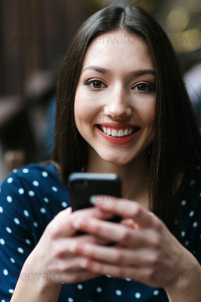 Beautiful girl types sms on the phone