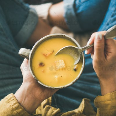 Female keeping mug of warming pumpkin cream soup, square crop