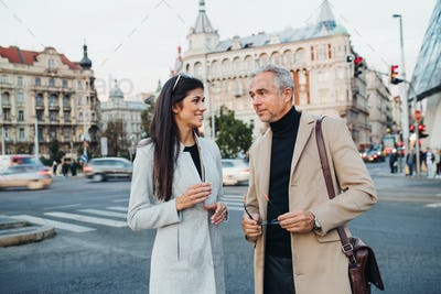 Man and woman business partners standing outdoors in city of Prague, talking.